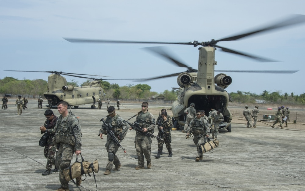 U.S. and Philippine Army soldiers unload from CH-47 Chinooks during refueling operations at the Combine Logistics Point for Operation Balikatan.