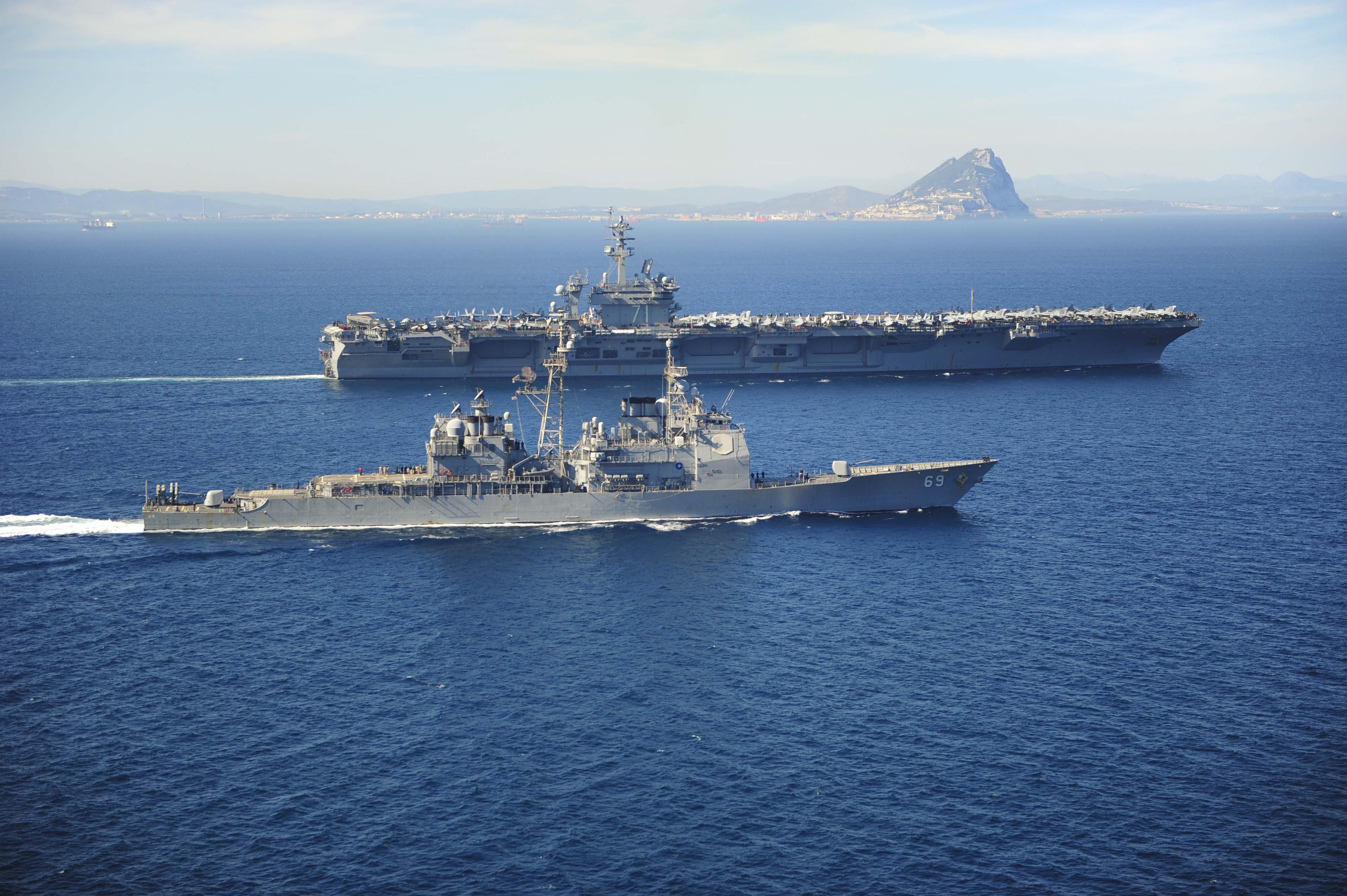 USS Vicksburg escorts USS Theodore Roosevelt past the Rock of Gibraltar.